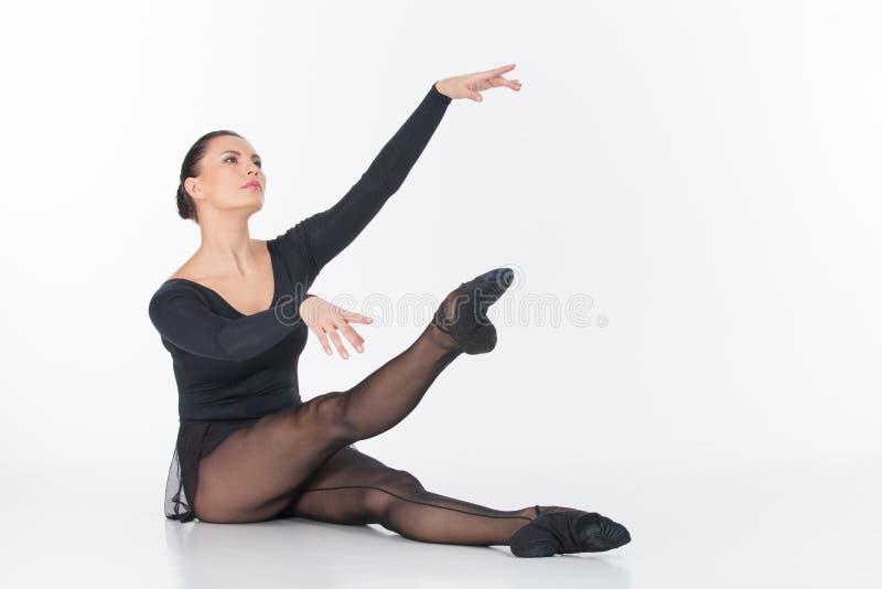 Danseur classique s'asseyant sur le plancher et l'étirage. image libre de droits