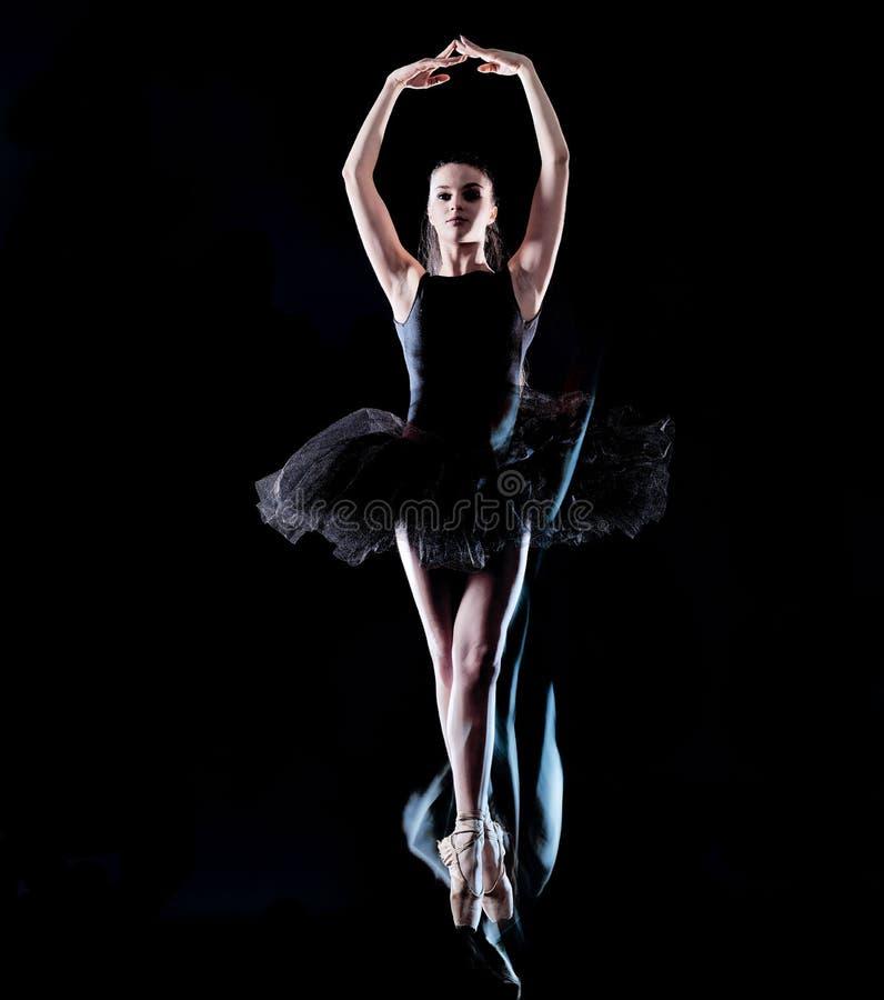 Danseur de ballerine de jeune femme dansant la peinture noire d'isolement de lumi?re de fond photo stock