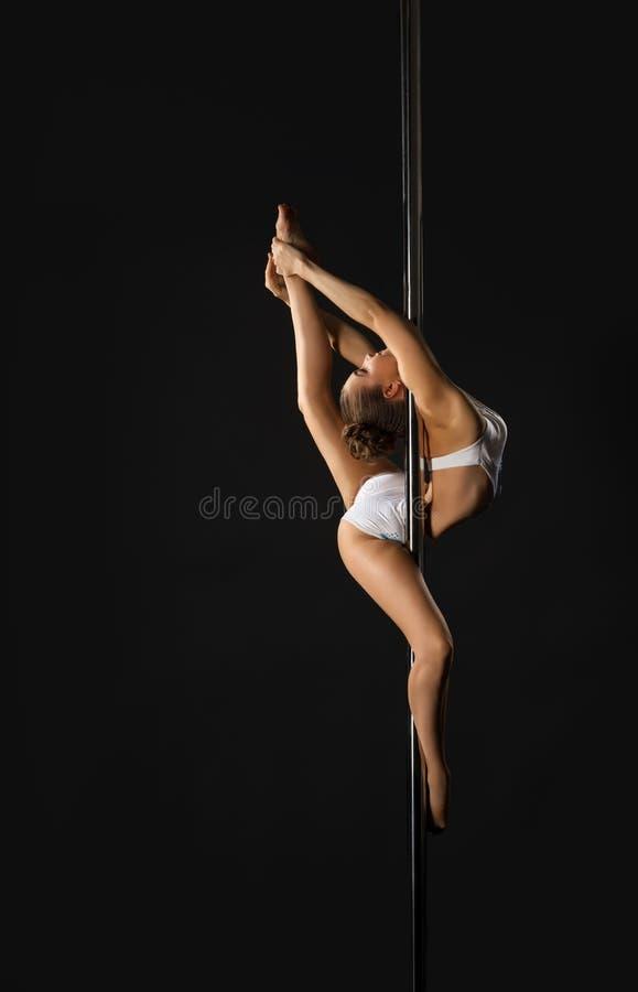 Danseur flexible s'exerçant sur le poteau dans le studio images libres de droits