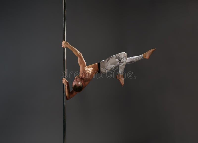 Danseur masculin au pylône dans le studio de danse de poteau photo stock