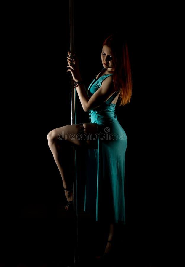 Danseur sexy de poteau de femme dans une longue robe de turquoise avec une fente sur un fond foncé photo libre de droits