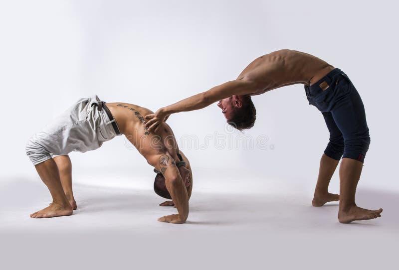 Danseurs acrobatiques masculins équilibrant dans le studio photos stock
