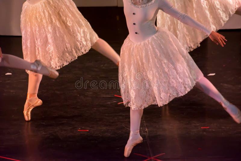 Danseurs classiques avec les robes classiques exécutant un ballet sur le fond de tache floue photos stock