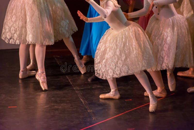 Danseurs classiques avec les robes classiques exécutant un ballet sur le fond de tache floue image libre de droits