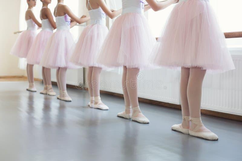 Danseurs classiques tenant le barre proche de ballet en position de base photographie stock libre de droits