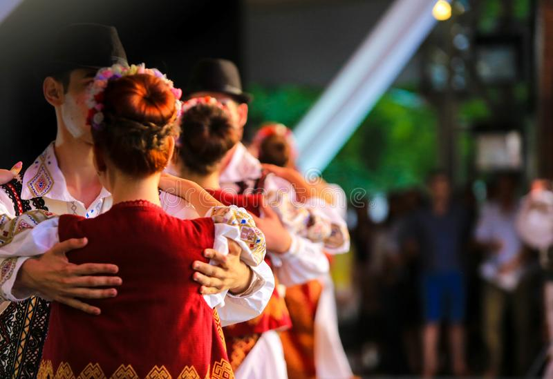 Danseurs méconnaissables folkloriques roumains sur l'étape Costumes nationaux photo stock