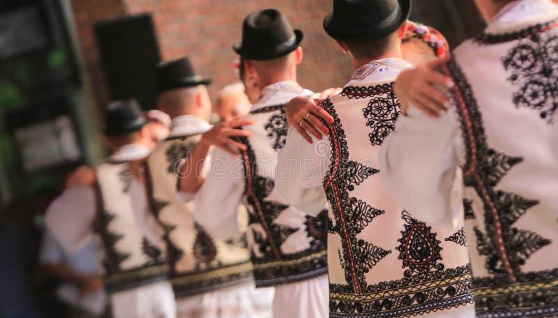 Danseurs méconnaissables folkloriques roumains sur l'étape Costumes nationaux photographie stock