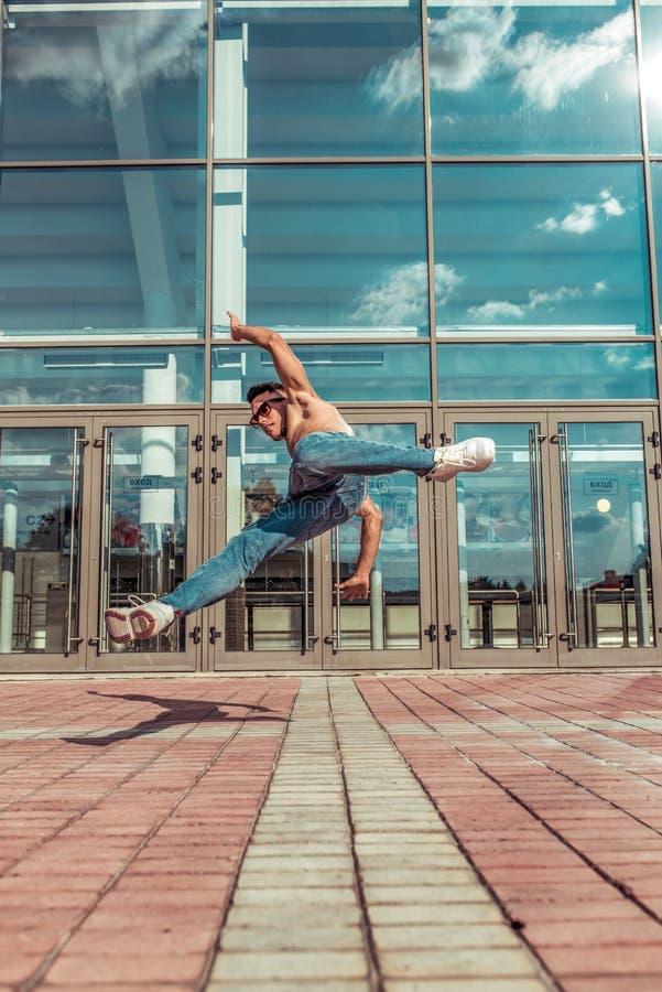 Danseuse de tambours, danse de break de l'acteur acrobate, hip hop L'été, en ville, le fond est recouvert de vitraux nuages Jeune photos stock