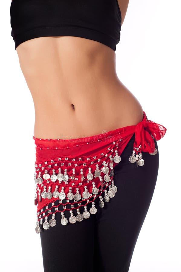 Danseuse du ventre portant un vêtement rouge de courroie et de séance d'entraînement de pièce de monnaie photos stock