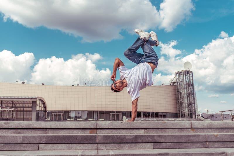Danseuse sur un seul bras danser casser la danse, hip-hop, artiste acrobate Ville d'été, fond de nuages Vie active chez les jeune photos stock