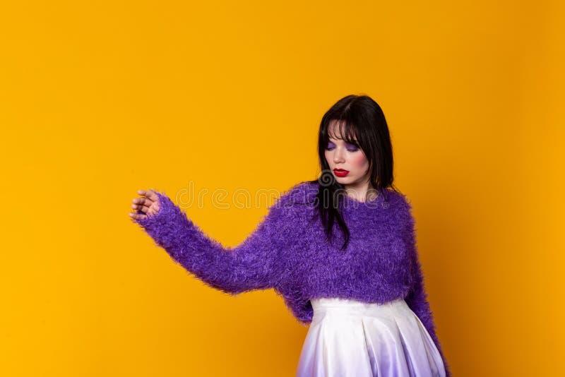 Dansflicka i trendig kläder på purpurfärgad bakgrund royaltyfri foto