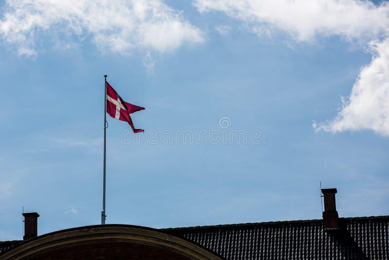 Dansk flagga i Köpenhamn över en blå himmel royaltyfri fotografi