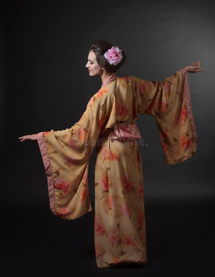 Danskvinna i traditionell japansk kimono på en svart backgrou royaltyfri fotografi