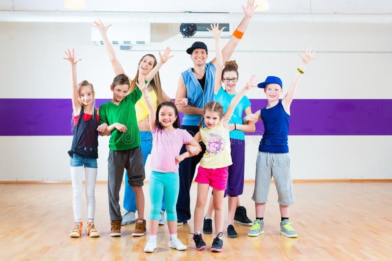 Danslärare som ger ungar Zumba konditiongrupp arkivbilder