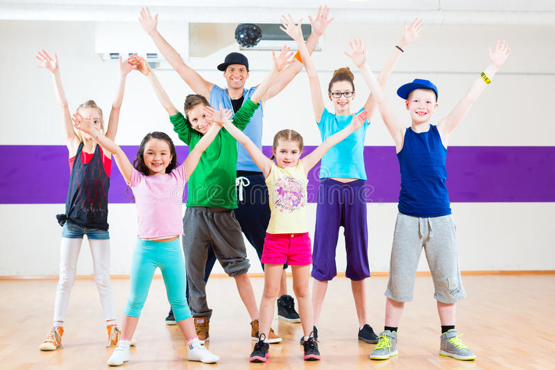 Dansleraar die de geschiktheidsklasse geven van jonge geitjeszumba stock afbeelding