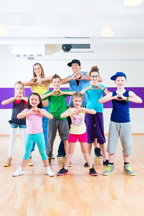 Dansleraar die de geschiktheidsklasse geven van jonge geitjeszumba royalty-vrije stock afbeelding