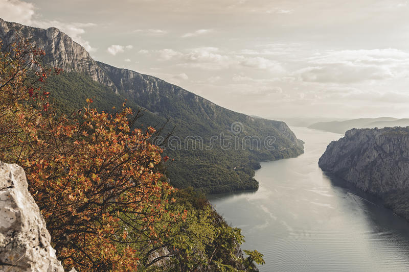 Danube in Djerdap National park, Serbia. Autumn colors at Danube and cliffs of a Miroc mountain at Djerdap National park during sunset, Vintage and dark toned royalty free stock image