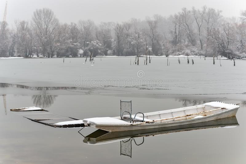 Danube island Šodroš near Novi Sad, Serbia. Colorful landscape with snowy trees, beautiful frozen river. A boats covered with sn. Ow or submerged royalty free stock photos