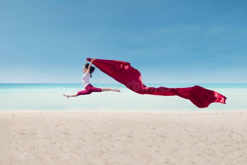 Danza asombrosa con la bandera roja en la playa imagen de archivo libre de regalías