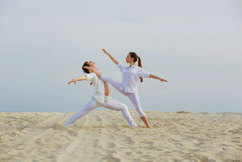 Danza atlética hermosa del entrenamiento de los pares en la playa imagenes de archivo