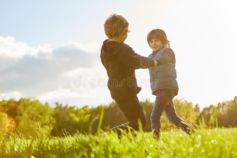 Danza de dos niños feliz en un prado fotos de archivo libres de regalías