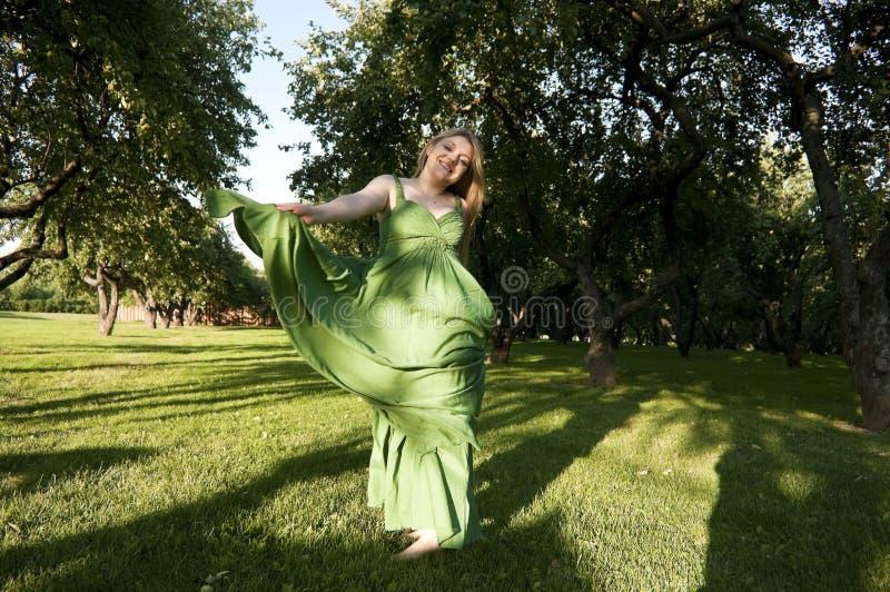 Danza sonriente de la muchacha en alineada verde en parque foto de archivo libre de regalías