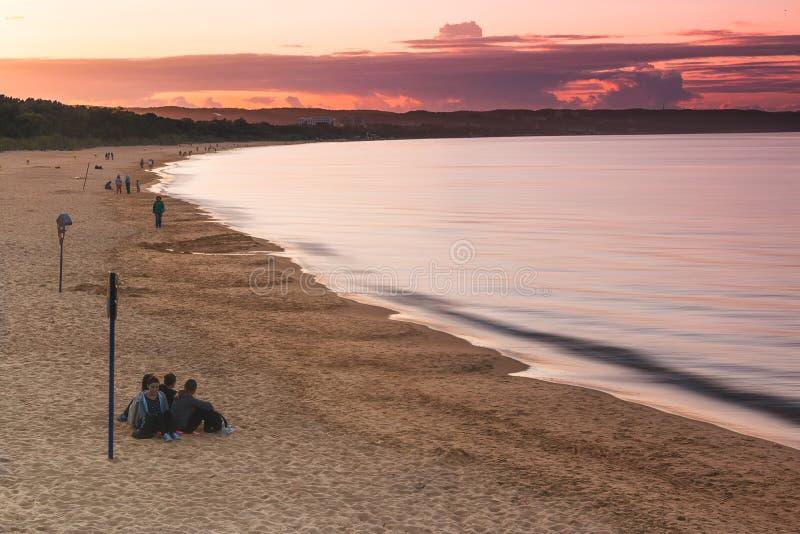 DANZICA, POLONIA, AGOSTO 2014 Tramonto di sorveglianza della gente sulla spiaggia baltica fotografia stock libera da diritti