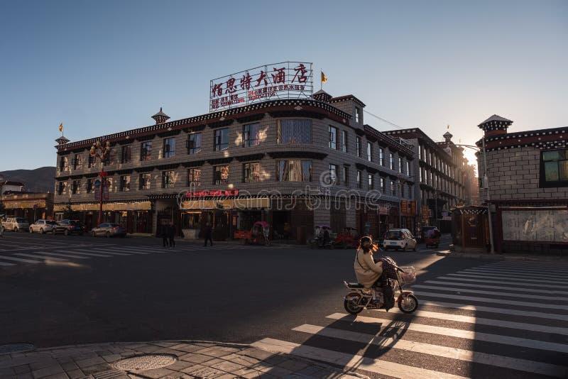 Daocheng arkitekturbyggnad med trafik på vägen på solnedgången fotografering för bildbyråer
