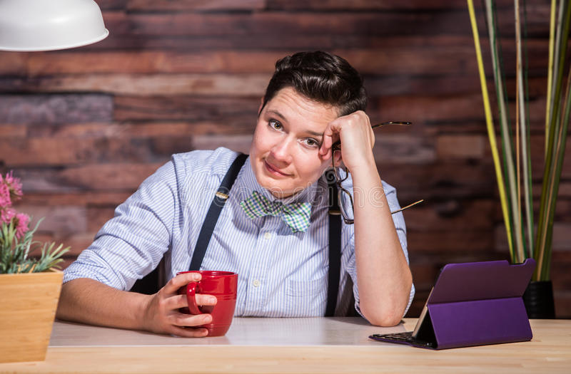 Dapper Businesswoman Listening. Woman with eyeglasses in hand at stylish office desk with a red cup royalty free stock photography