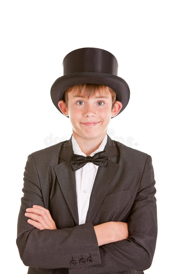 Dapper confident young boy in a top hat. Bow tie and black jacket standing grinning at the camera with folded arms, isolated on white royalty free stock image