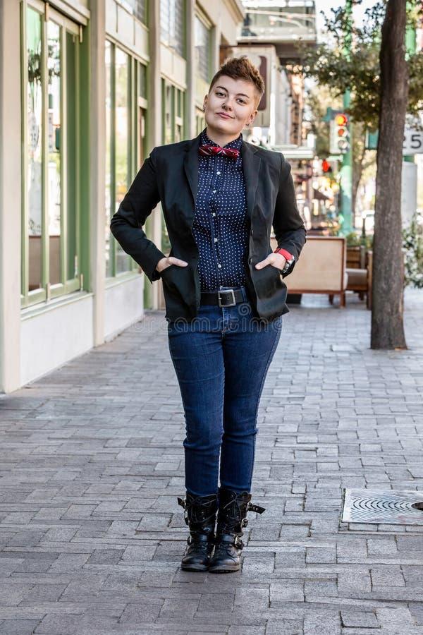 Dapper Gender Fluid Young Woman. Dapper young gender fluid woman on city sidewalk stock images
