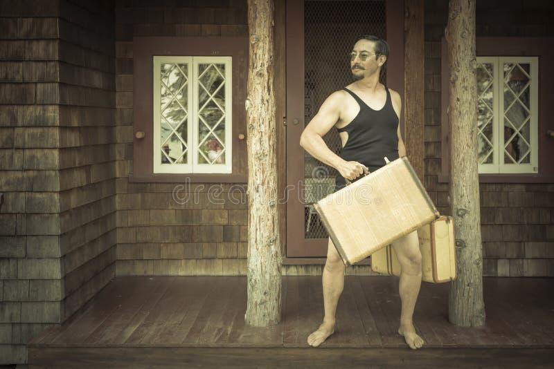 Dapper Gentleman in 1920's Era Swimsuit Holding Suitcases on. Goofy Gentleman Dressed in 1920's Era Swimsuit Holding Suitcases on Porch of Cabin royalty free stock image