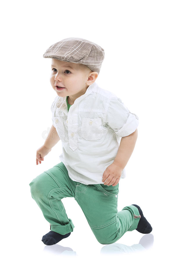 Dapper little boy in a cute outfit. With a cloth cap, white shirt and green trousers rising to his feet with a look of delighted anticipation, isolated on white royalty free stock photography
