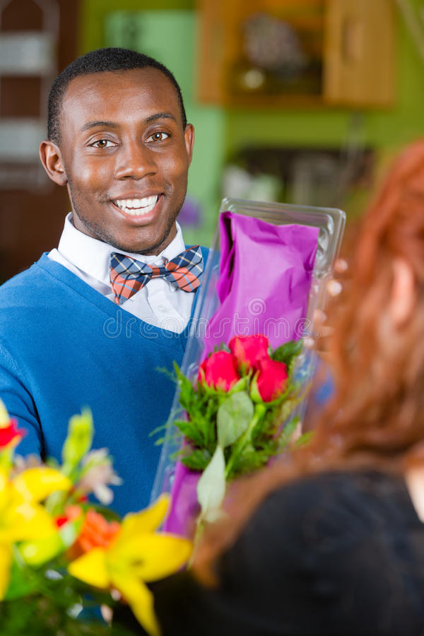 Dapper Man in Flower Shop Buys Roses. Dapper men purchasing roses at a florist shop royalty free stock images