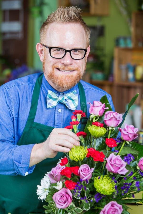 Dapper Man Working in Flower Shop. Dapper man wearing eyeglasses and apron creating a flower arrangement stock image
