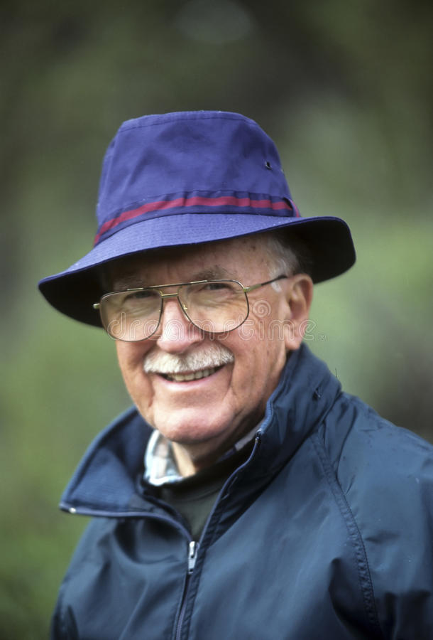 Dapper senior man in blue hat. Jaunty older man in blue hat and with a mustache royalty free stock images