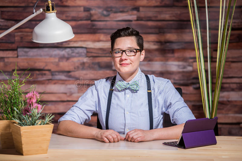 Dapper Woman in Hipster Office with Tablet. Dapper bowtie wearing woman at stylish office desk with tablet stock image