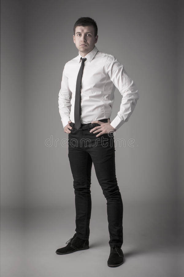 Dapper young business man with hands on hips. Handsome well-dressed young man full-length standing with hands on hips, looking seriously straight to the camera stock images