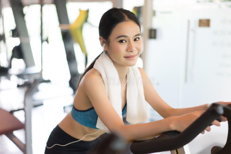 Dar certo de sorriso da jovem mulher muscular na bicicleta de exercício em foto de stock