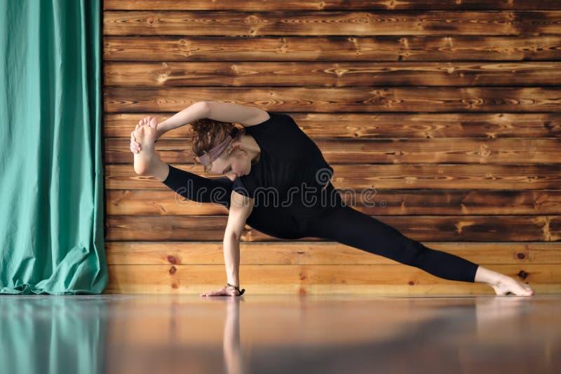 Dar certo encaracolado da mulher, fazendo a pose lateral da prancha com esticão imagens de stock