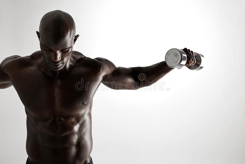 Dar certo modelo da aptidão africana muscular com pesos fotografia de stock royalty free