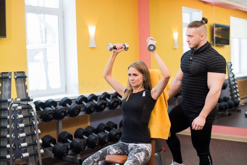 Dar certo no gym: Mulher bonita de Yong que faz o exercício do peso que senta-se no banco quando instrutor muscular que olha e fotos de stock royalty free
