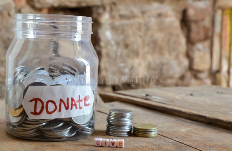 Dar doação, pote de dinheiro com um rótulo com a palavra doações e madeira, dar doação de texto escrito em madeira, moedas em pot foto de stock royalty free