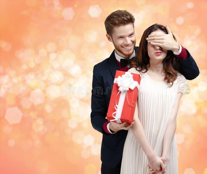 Dar um homem do presente de Natal fecha os olhos de sua amiga imagem de stock