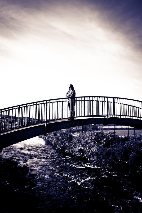Dar uma volta mostrado em silhueta mulher em uma ponte moderna fotos de stock royalty free