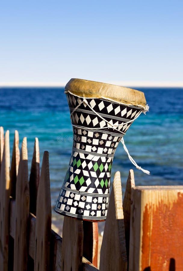 Tamburo etnico con un fondo del mare. darbuka. fotografia stock