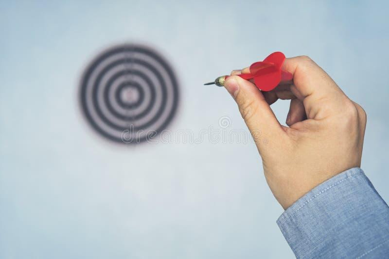 Dardo vermelho no ponto da mão do homem a visar na parede azul, foco seletivo no alvo do dardo, conceito a ganhar fotografia de stock royalty free
