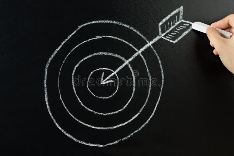 Dardo y flecha del dibujo de la persona en la pizarra fotografía de archivo libre de regalías