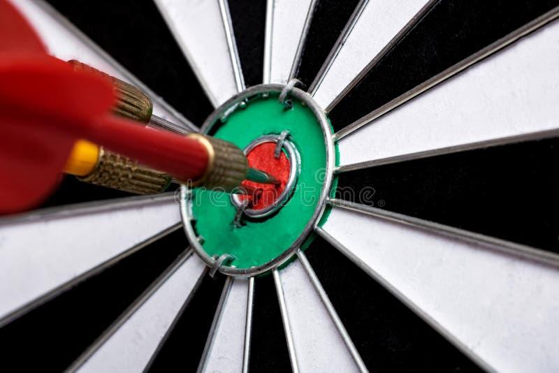 Dardos e close-up dos dardos, batendo o alvo imagem de stock