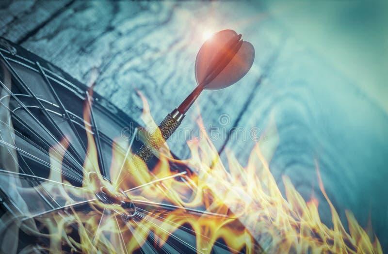 Dardos no alvo na parede de madeira com chama, investimento empresarial que confiam na precisão afastado fotografia de stock royalty free